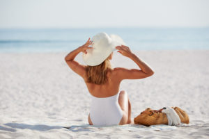 woman-looking-at-view-sitting-on-beach-wearing-one-piece-bathing-suite-img-blog-300x200 Fight Back Against Sun Damage