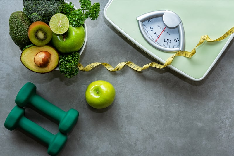 Items associated with weight loss such as fruits, vegetables, weights, measuring tape, and a scale.